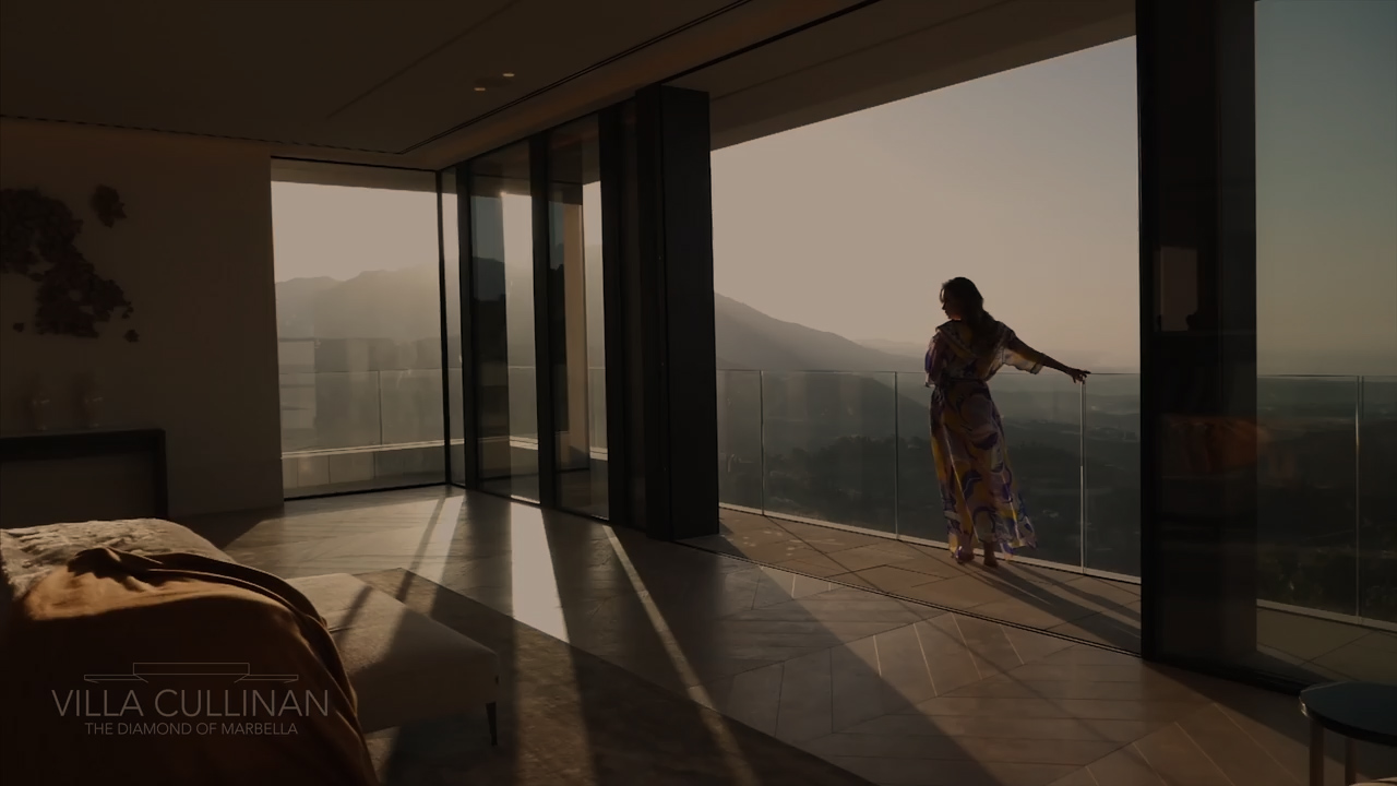 woman standing near large windows overlooking view